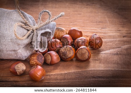 hazelnuts and sack on vintage wooden board food and drink concept  - stock photo