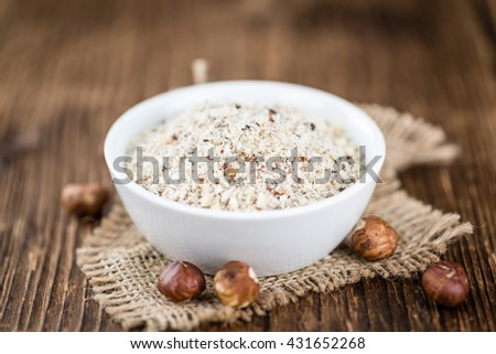 Hazelnuts (grounded) on vintage wooden background (selective focus; close-up shot) - stock photo