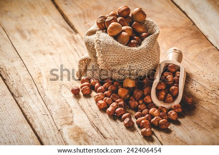 Hazelnuts in a rural bag on a wooden table and a spoon for scooping. - stock photo