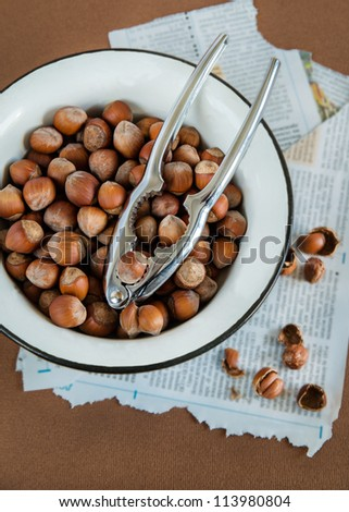 Hazelnuts in a white bowl, metal nutcracker and cracked nuts on the side, brown background