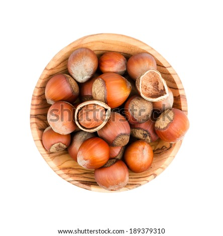 Hazelnuts in a wooden bowl isolated on white background - stock photo