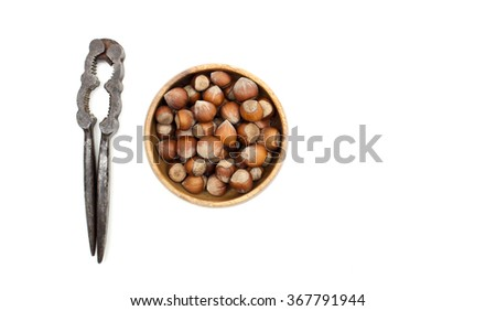 Hazelnuts in a wooden bowl with nutcracker. - stock photo