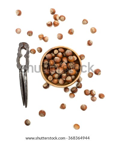 Hazelnuts in a wooden case with nutcracker.  - stock photo