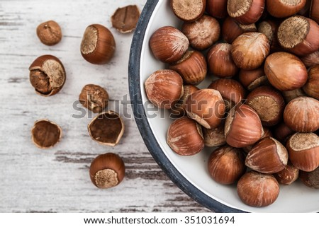 Hazelnuts in enamel bowl on white wooden table, top view