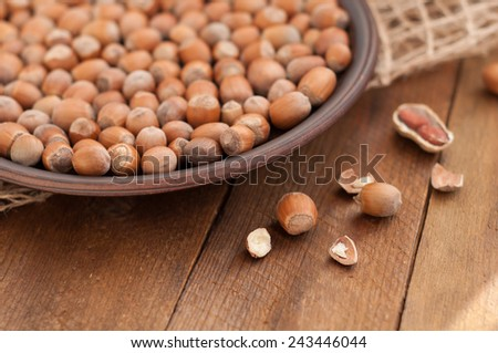 Hazelnuts on a plate, and peanut pods kernel hazelnut on wooden brown background. Selective focus - stock photo