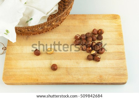 Hazelnuts on wooden chopping board over white ground