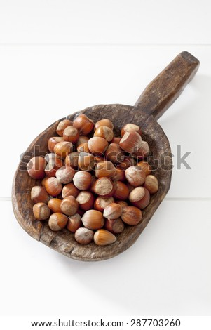 Hazelnuts on wooden spoon on white background