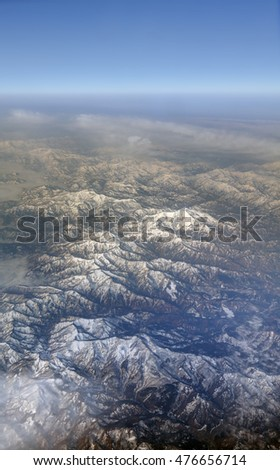 HDR Aerial photo of the japanese landscape with clouds, mountains and landscape with snowy patches and a view stretching all the way to the horizon
