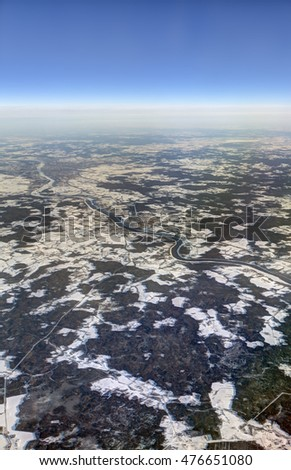 HDR Aerial photo of the landscape with clouds, snowy patches, a larger river in a canyon and a view stretching all the way to the horizon