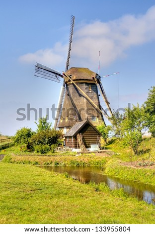 hdr image of a traditional windmill in Holland on a sunny day in summertime