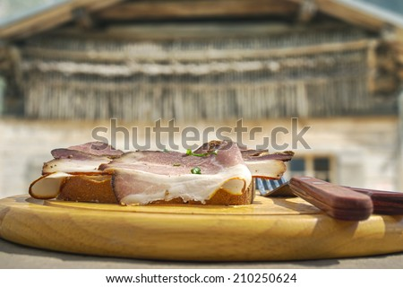 HDR image of cold cuts on wooden plate in front of a mountain hut in the alps - stock photo