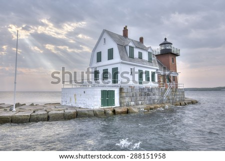 HDR image of Rockland Harbor Breakwater Lighthouse at high tide under cloudy sky with rays of sunlight shining down on ocean in Maine - stock photo
