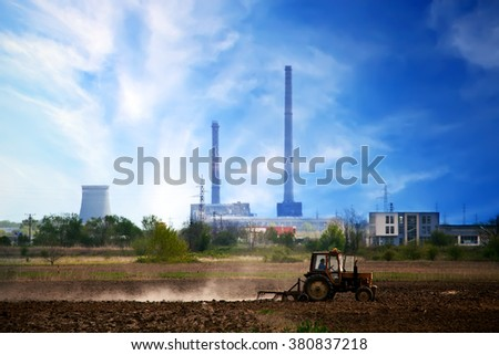 HDR landscape sunset over the cultivated farmland, tractor near the industrial zone  - stock photo
