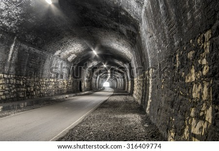 HDR old brick built railway tunnel with soot covered walls and with the exit glowing in the distance - stock photo