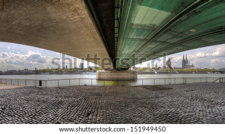 HDR Panorama under the Deutzer Bridge looking back to central Cologne. - stock photo