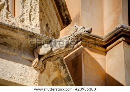 HDR photo of a historic stone gargoyle on the edge of an old house in Mdina city, historic capital of Malta.