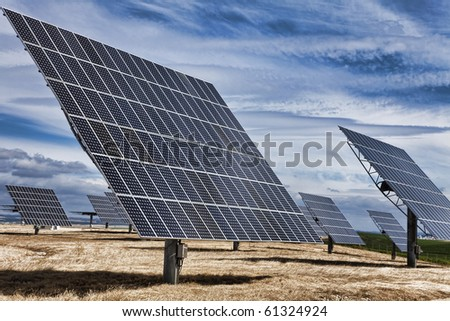 HDR photograph showing field of photovoltaic solar panels providing alternative green energy - stock photo