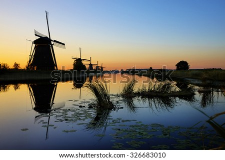 HDR picture of sunrise with windmills of Kinderdijk in the province of Zuid-Holland, the Netherlands - stock photo
