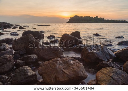 HDR sunset over rock in sea beach - stock photo