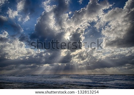 HDR sunset Sun rays through clouds on a winter beach - stock photo