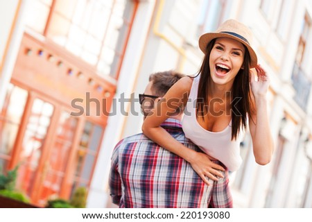 He always makes me smiling. Rear view of young cheerful man carrying his beautiful girlfriend on shoulder while walking by the street - stock photo