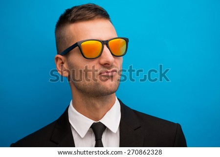 He do not afraid of bright sun. Handsome in red glasses and black suit on blue background - stock photo
