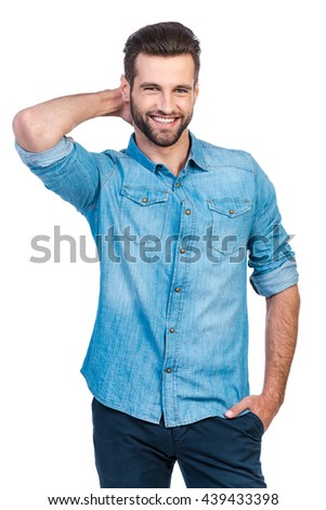 He got candid smile. Confident young handsome man in jeans shirt holding hand behind head and smiling while standing against white background  - stock photo