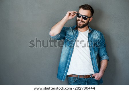 He got charming personality. Cheerful young man adjusting eyewear and looking away while standing against grey background - stock photo