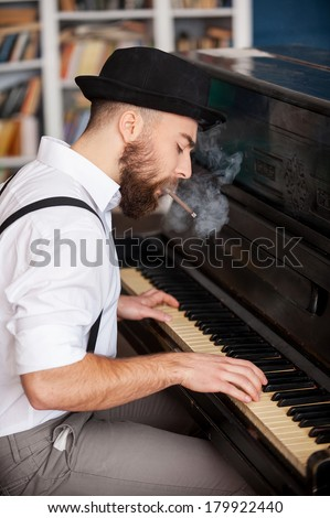 He got his own technique. Profile of handsome young bearded men playing piano and smoking cigarette - stock photo
