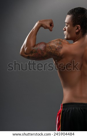 He got perfect body. Rear view portrait of young shirtless African man showing his bicep with tattoo while standing against grey background  - stock photo