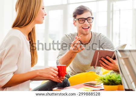 He got so many ideas. Cheerful young man holding note pad and gesturing while sitting in office with his colleagues - stock photo