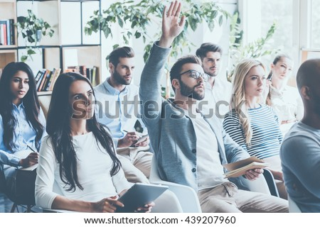 He got some questions. Group of young people sitting on conference together while one man raising his hand  - stock photo