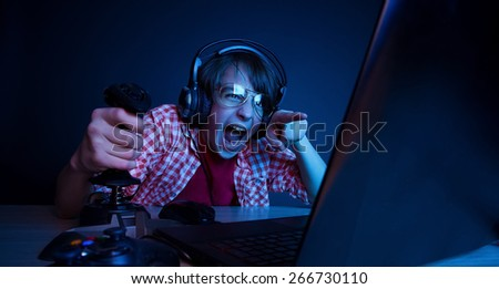 He had revenge in video games. In blue light of monitor emotional kid play computer games online. - stock photo