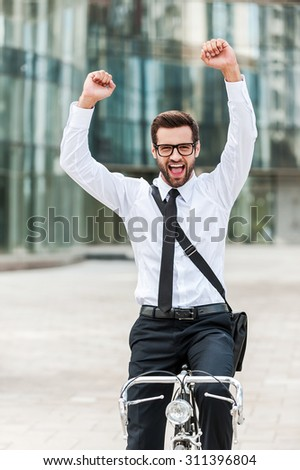 He has great mood this morning. Excited young businessman expressing positivity while riding on his bicycle - stock photo
