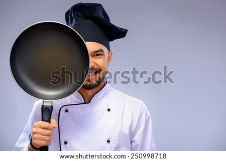 He is a best chef ever. Closeup portrait of handsome cook covering a half of his face with a frying pan and smiling while standing against grey background with copy space - stock photo