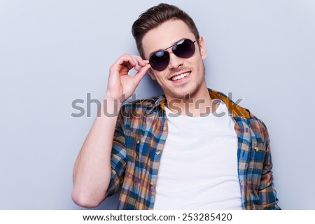 He is a real macho. Handsome young man in shirt adjusting his sunglasses and looking at camera while standing against grey background  - stock photo