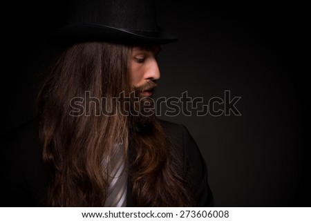 He is a rock star and he can play guitar. Hipster with long hair and beard, weared in topper and black suit on dark background - stock photo