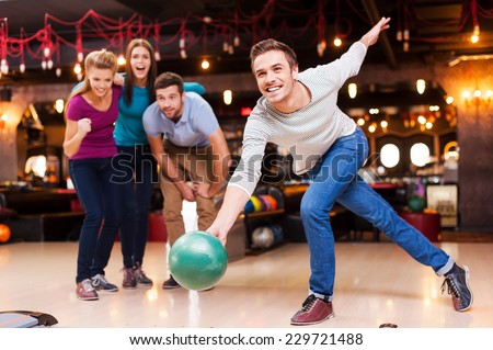 He is a winner. Handsome young men throwing a bowling ball while three people cheering   - stock photo