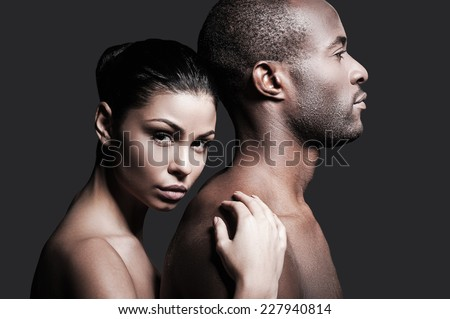He is absolutely mine. Beautiful Caucasian woman bonding to back of handsome African man and looking at camera while both standing against grey background  - stock photo