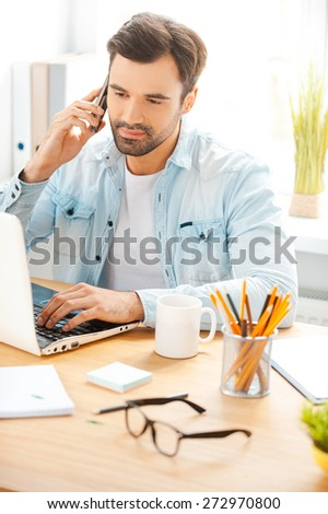 He is always hard at work. Handsome young man in shirt talking on the telephone and working on laptop while sitting at his working place - stock photo