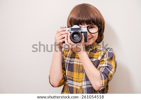 He is fond of shooting. Little boy in eyewear holding camera and smiling while standing against grey background - stock photo