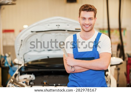 He is ready to work. Confident young man in uniform holding a wrench an smiling while standing in workshop with car in the background
