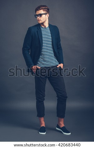 He is so stylish. Full length of confident young handsome man in sunglasses keeping hands in pockets and looking away while standing against grey background - stock photo