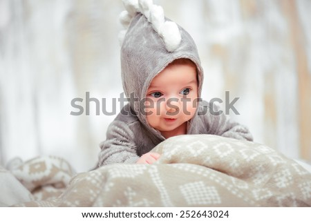 He is such a funny little guy. Closeup of a cute little baby in dinosaur bodysuit lying on the blanket - stock photo
