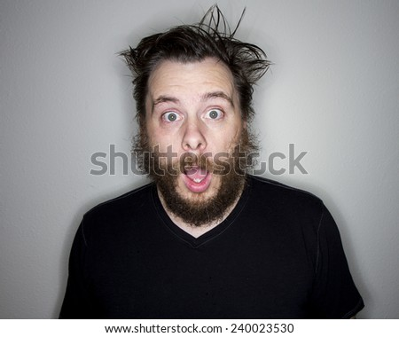 He is surprised at something so makes a shocked look on his face - stock photo