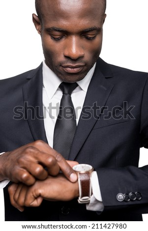 He knows that time is money. Serious young African man in formalwear checking time while looking at his watch and standing isolated on white background  - stock photo