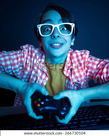 He like play and win video games. In blue light of monitor emotional kid play computer games online. - stock photo