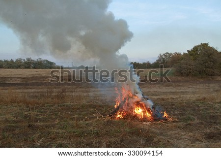 He lit the fire of autumn grass on the field. Autumn a lot of smoke fire - stock photo