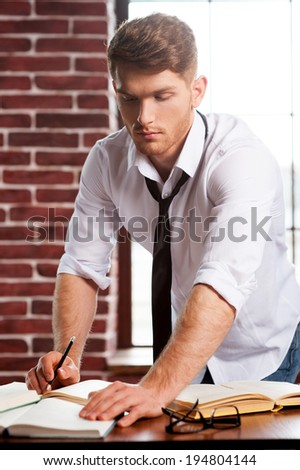 He loves studying. Handsome young man in shirt and tie writing something in note pad and reading while bonding over the desk - stock photo