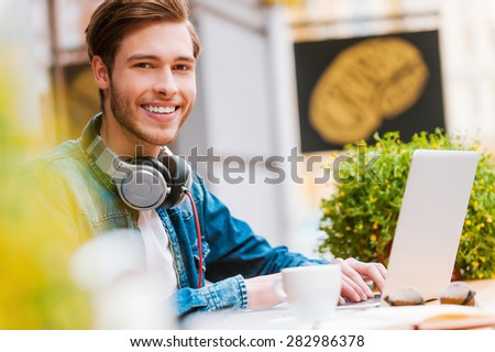 He loves such spending his day. Happy young man working on laptop and smiling at camera while sitting at sidewalk cafe - stock photo